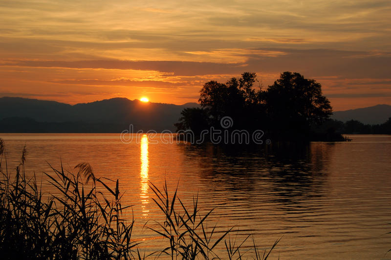 Silhouetted small island in lake at sunrise stock photography
