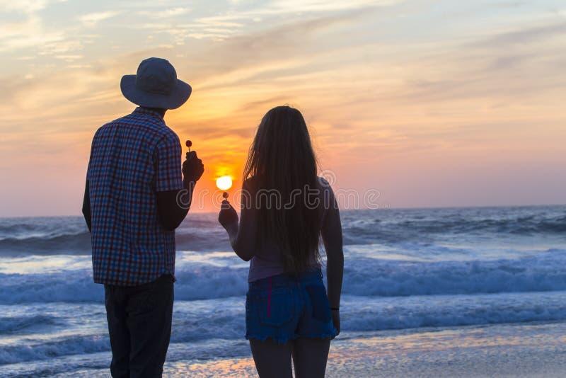 Silhouetted soluppgång för flickamanstrand royaltyfria bilder
