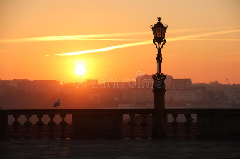 Silhouetted street lamp at sunset. Porto. Portugal. A silhouetted street lamp at sunset, View from the Cathedral square. Porto. Portugal stock image