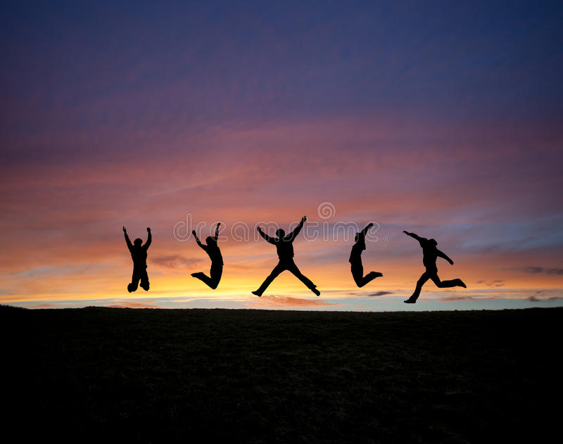 Silhouetted teens jumping in sunset. Sky royalty free stock photo