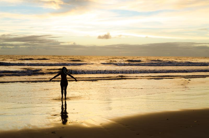 A silhouetted woman with open arms near the sea on a beach with the sun rising and the sunrays reflecting in the sea water. stock photo