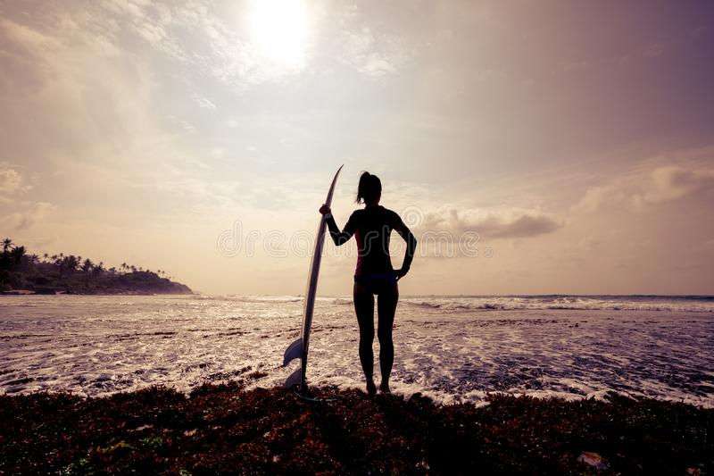 Silhouetted young woman surfer girl with white surfboard stock photos