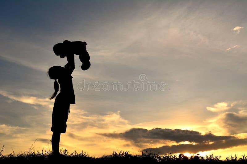 Silhouetteer een meisje met teddybeer stock foto
