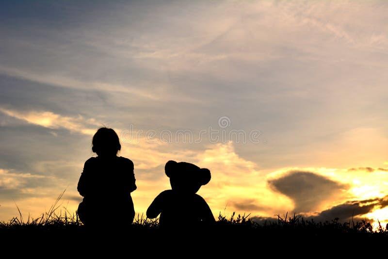 Silhouetteer een meisje met teddybeer stock fotografie