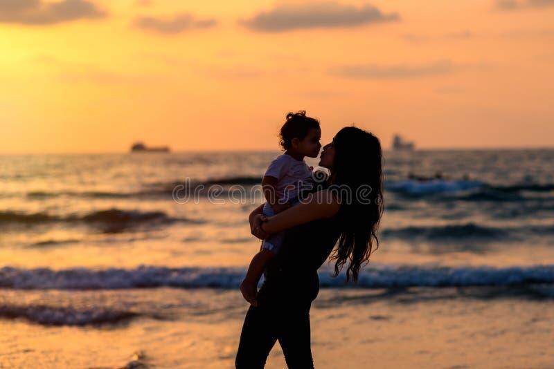 Silhouetteert jonge moeder met dochter het spelen en het kussen op het strand bij de hemelachtergrond van de zonsondergangavond G royalty-vrije stock foto