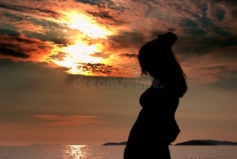 Silhouettekvinna och solnedgång på stranden royaltyfria bilder