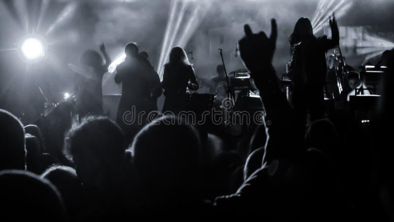 Silhouetten der Konzertbesucher vor hellen Lampen das Pop-Rock-Konzert vor der Bühne Hände mit gespenstischen Hörnern lizenzfreie stockfotografie