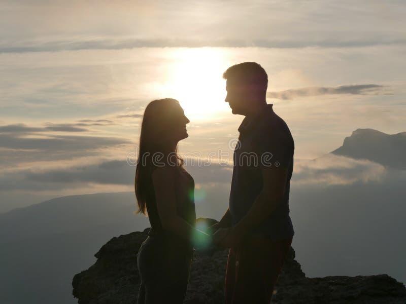 Silhouetten die van jong paar zich op een berg bevinden en aan elkaar op mooie zonsondergangachtergrond kijken Liefde van kerel royalty-vrije stock afbeelding