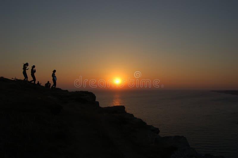 Silhouetten op berghelling van zonsondergang en overzees royalty-vrije stock foto