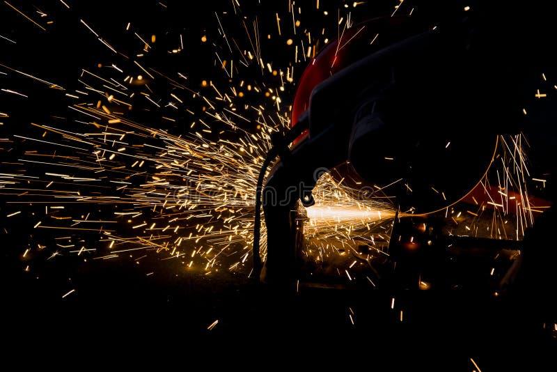 Silhouetten van Arbeider en vonken van vuur terwijl het malen van ijzer stock foto