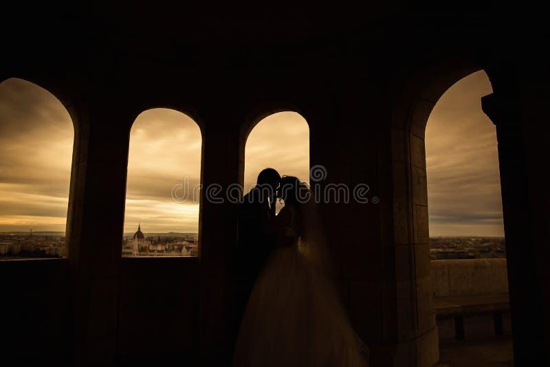 Silhouetten van bruid en bruidegom die zich op de achtergrond van de nachtstad bevinden en teder elkaar zonsondergang bekijken royalty-vrije stock fotografie