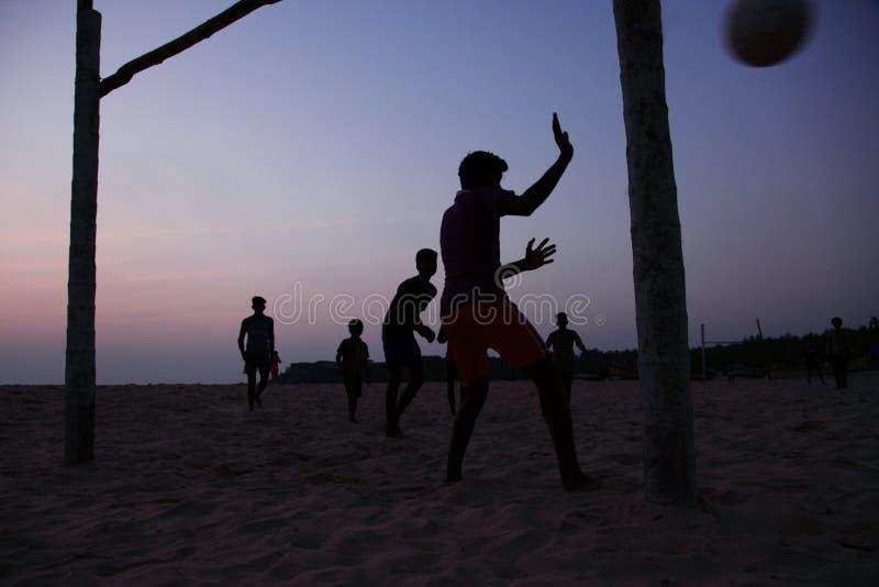 Silhouetten van de voetbal van het mensenspel in het strand royalty-vrije stock foto's