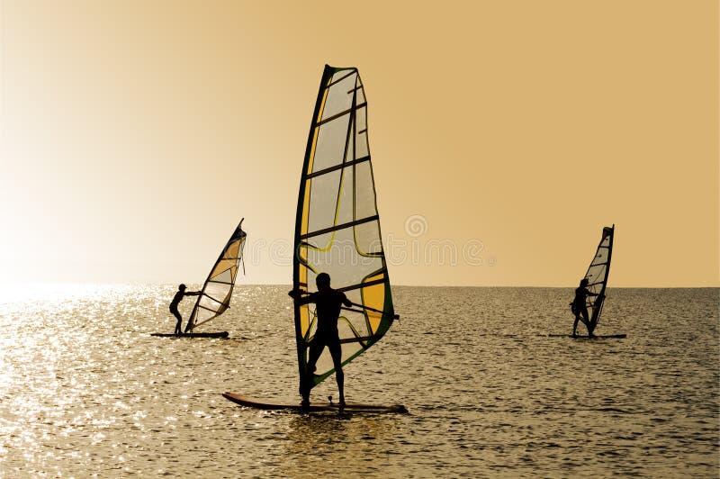 Silhouetten van drie windsurfers stock fotografie