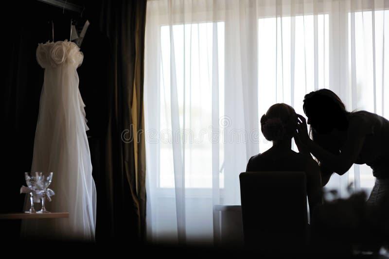 Silhouetten van een bruid en een grimeur royalty-vrije stock foto