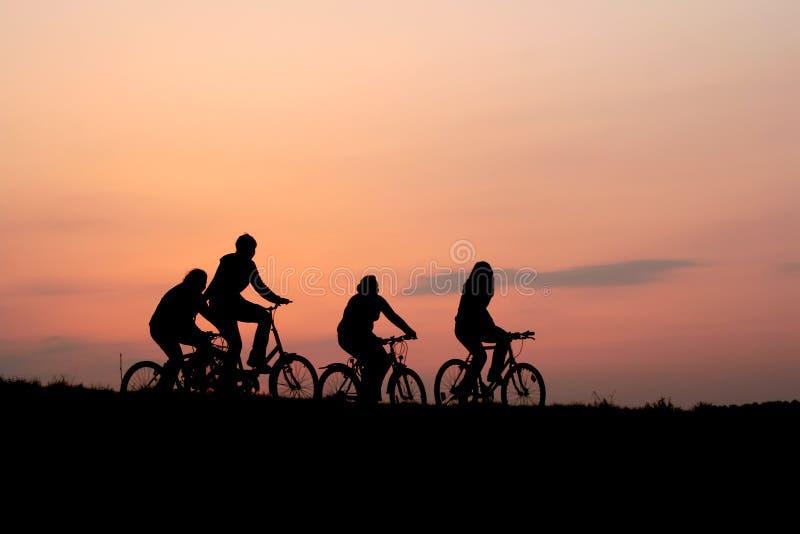 Silhouetten van een familie op fietsen royalty-vrije stock afbeelding