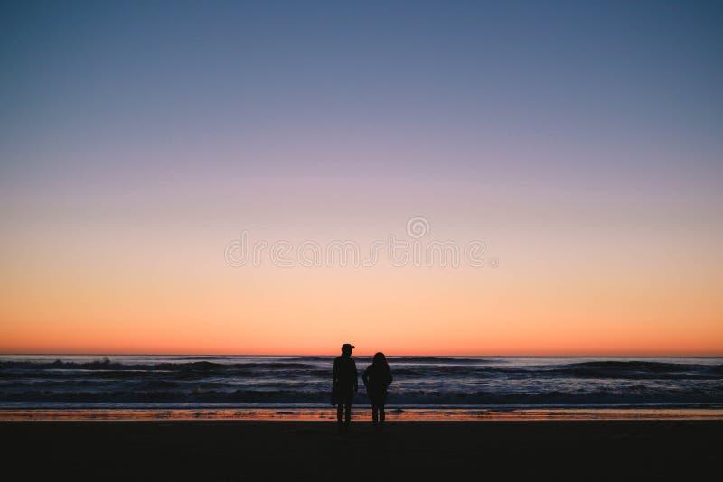 Silhouetten van een paar die zich op het strand bevinden en van de mooie zonsondergang genieten royalty-vrije stock foto's