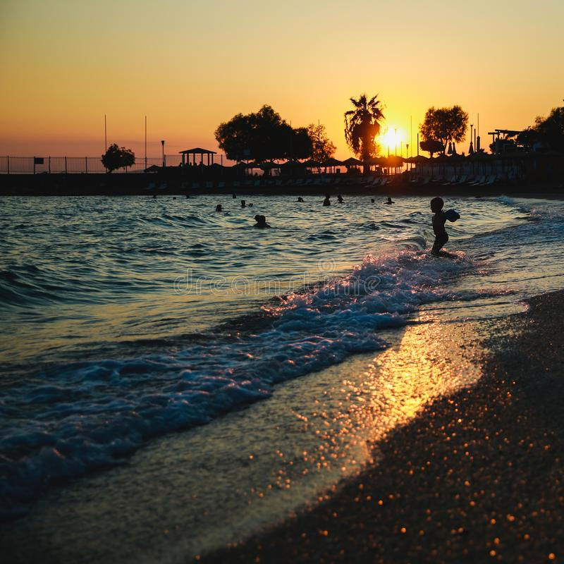 Silhouetten van gelukkige mensen die en in het overzees bij zonsondergang, concept over het hebben van pret op het strand zwemmen stock foto