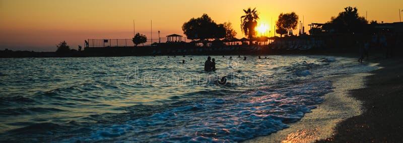 Silhouetten van gelukkige mensen die en in het overzees bij zonsondergang, concept over het hebben van pret op het strand zwemmen stock foto's