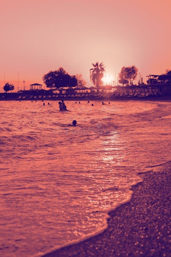 Silhouetten van gelukkige mensen die en in het overzees bij zonsondergang, concept over het hebben van pret op het strand zwemmen stock fotografie
