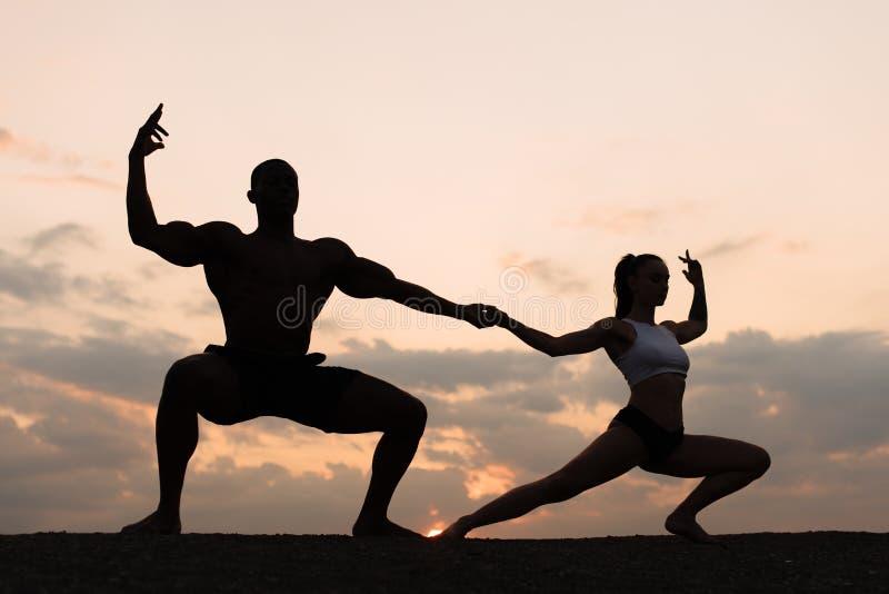 Silhouetten van gemengde paarturners die op zonsondergang dansen Gunst en schoonheid van menselijk lichaam royalty-vrije stock foto