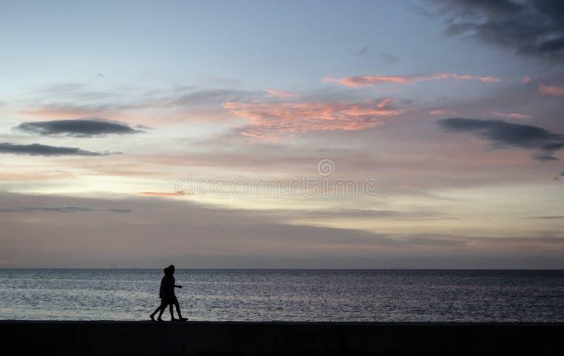 Silhouetten van het Paar die van jonge geitjes bij de strandboulevard lopen stock foto's