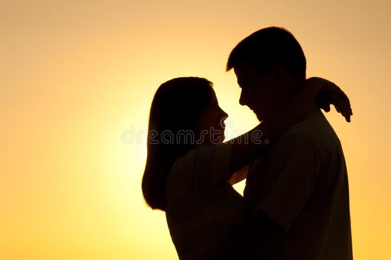 Silhouetten van jong paar in liefde bij zonsondergang stock fotografie