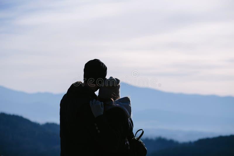 Silhouetten van jong paar in liefde die zich op de bovenkant van berg bevinden royalty-vrije stock afbeelding