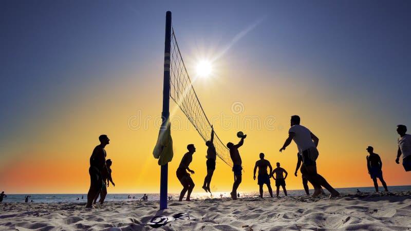 Silhouetten van jonge mensen die volleyball op Varkala-strand spelen bij zonsondergang royalty-vrije stock afbeeldingen