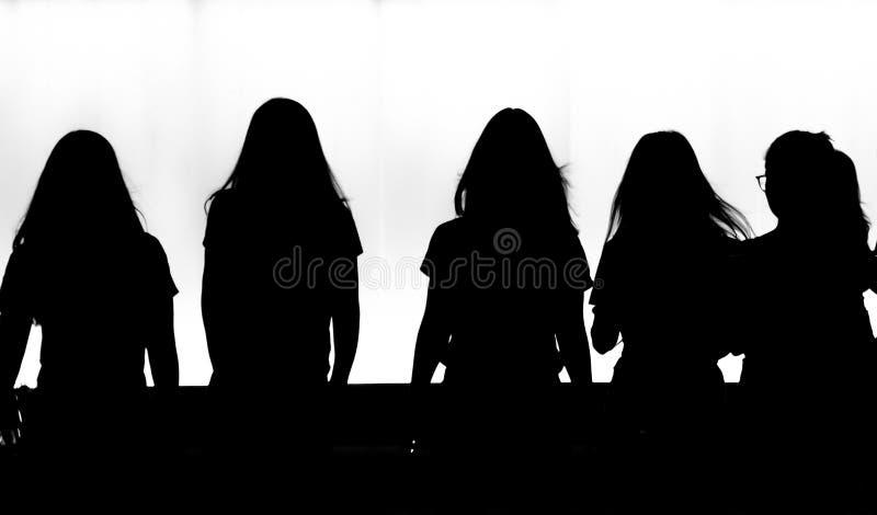 Silhouetten van jonge vrouwen die in motieonduidelijk beeld lopen in de nacht stock fotografie