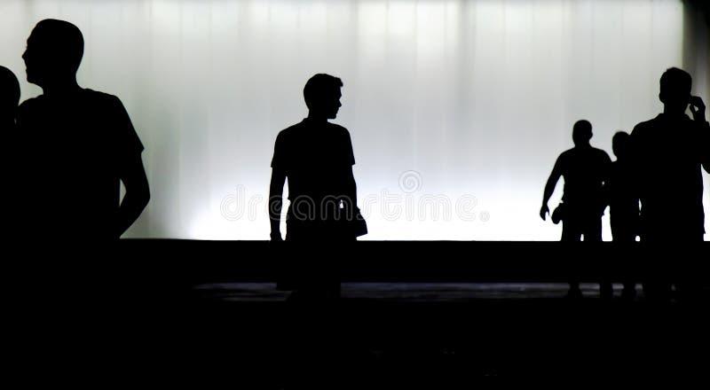 Silhouetten van jongeren die in motieonduidelijk beeld lopen in de nacht stock fotografie