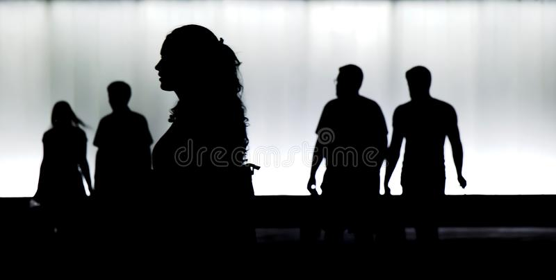 Silhouetten van jongeren die in motieonduidelijk beeld nigh lopen in stock foto