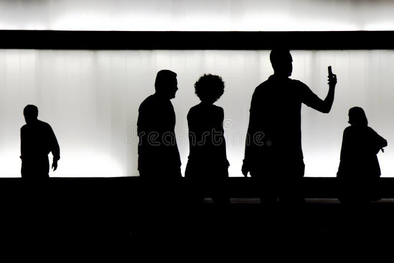 Silhouetten van jongeren die in motieonduidelijk beeld nigh lopen in royalty-vrije stock fotografie