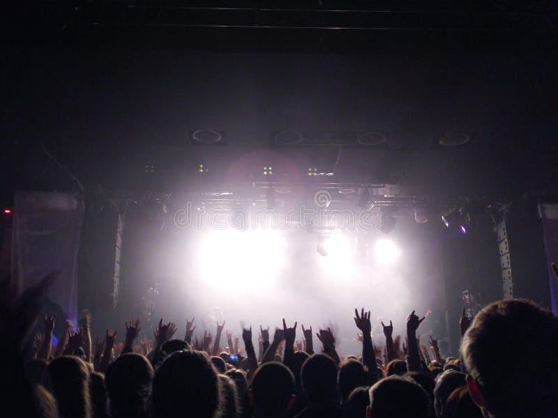 Silhouetten van jongeren met de opgeheven handen omhoog vóór een scène bij een overleg Popgroep Helder licht op het stadium stock fotografie