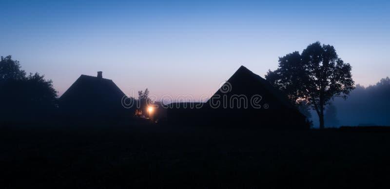 Silhouetten van Letse boerderij bij zonsondergang stock afbeeldingen