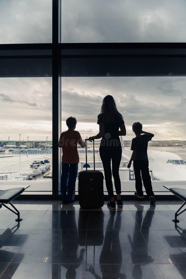 Silhouetten van mamma met jonge geitjes in terminal die op vlucht wachten stock afbeeldingen