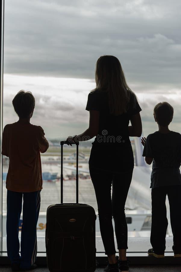 Silhouetten van mamma met jonge geitjes in terminal die op vlucht wachten royalty-vrije stock afbeelding