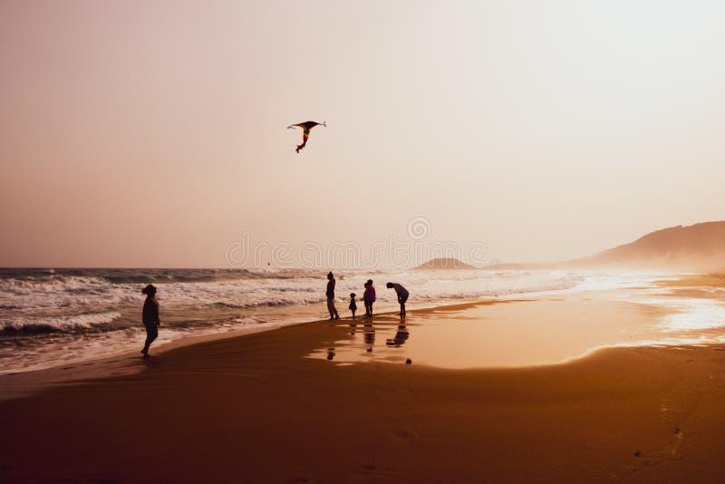 Silhouetten van mensen die en een vlieger in zandig Gouden Strand, Karpasia, Cyprus spelen vliegen stock afbeelding