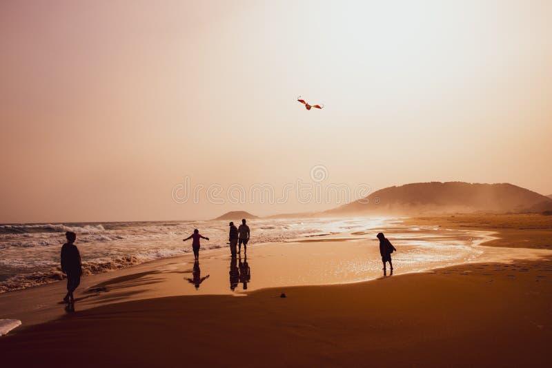 Silhouetten van mensen die en een vlieger in zandig Gouden Strand, Karpasia, Cyprus spelen vliegen royalty-vrije stock fotografie