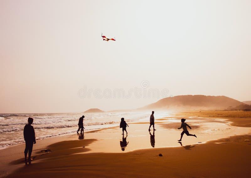 Silhouetten van mensen die en een vlieger in zandig Gouden Strand, Karpasia, Cyprus spelen vliegen royalty-vrije stock afbeelding
