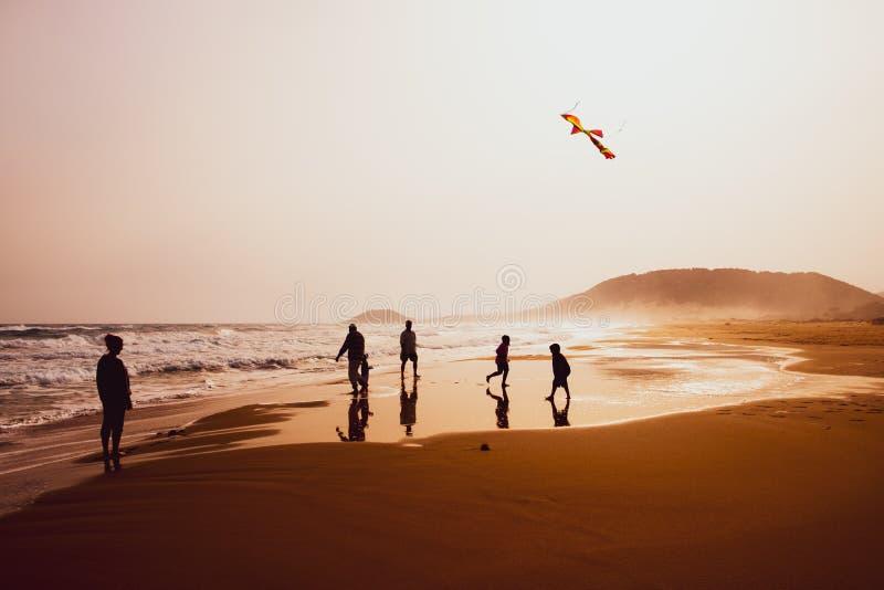 Silhouetten van mensen die en een vlieger in zandig Gouden Strand, Karpasia, Cyprus spelen vliegen royalty-vrije stock foto's