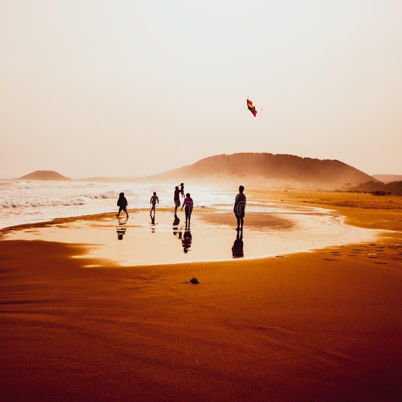 Silhouetten van mensen die en een vlieger in zandig Gouden Strand, Karpasia, Cyprus spelen vliegen stock fotografie