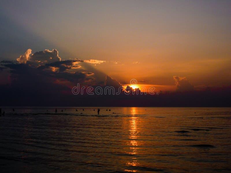 Silhouetten van mensen die in het overzees op een zonsondergang bathering backgroun stock foto's