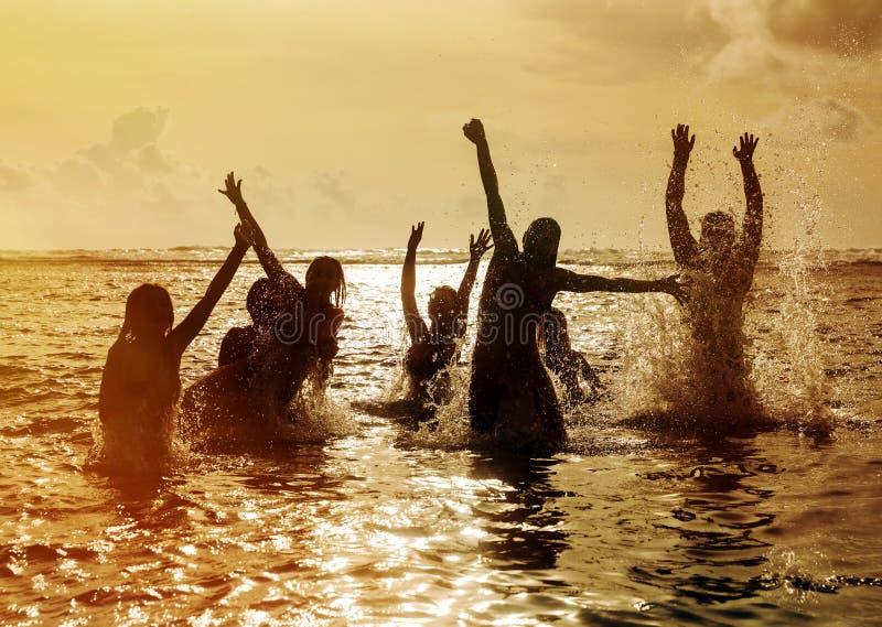 Silhouetten van mensen die in oceaan springen royalty-vrije stock fotografie