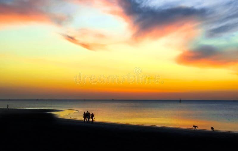 Silhouetten van mensen die op het strand bij zonsondergang lopen Epische dramatische zonsondergang royalty-vrije stock foto