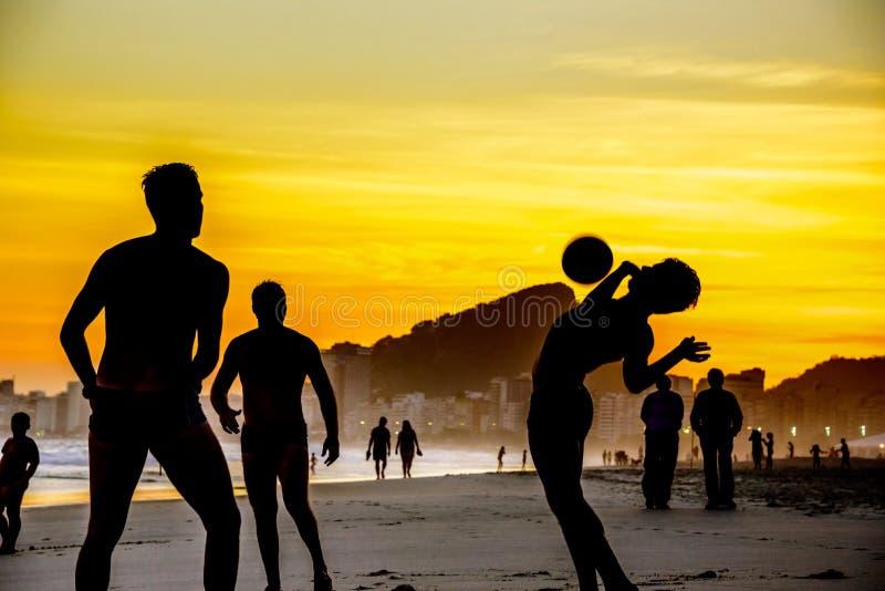 Silhouetten van mensen die strandvoetbal op de achtergrond van mooie gouden zonsondergang spelen bij Copacabana-strand, Rio de Ja royalty-vrije stock foto