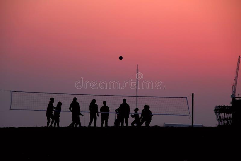 Silhouetten van mensen die volleyball spelen bij zonsondergang stock fotografie