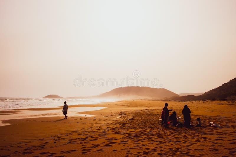 Silhouetten van mensen die in zandig Gouden Strand, Karpasia, Cyprus spelen royalty-vrije stock afbeeldingen