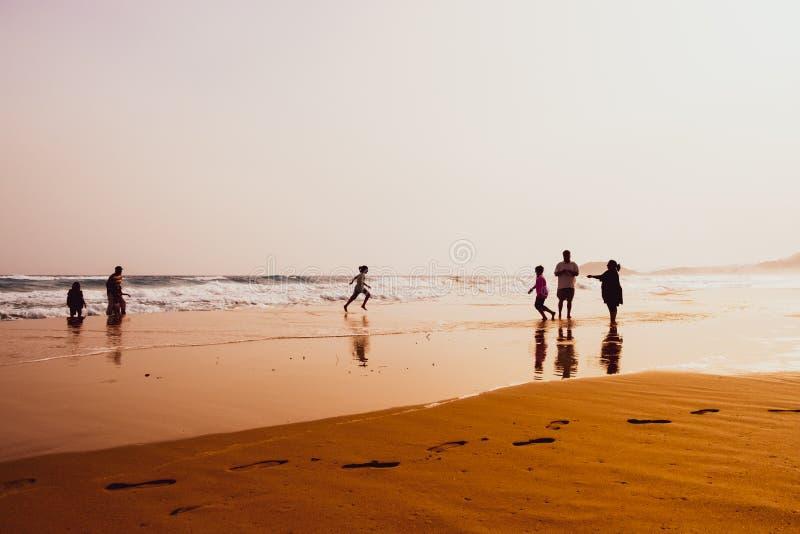 Silhouetten van mensen die in zandig Gouden Strand, Karpasia, Cyprus spelen royalty-vrije stock fotografie