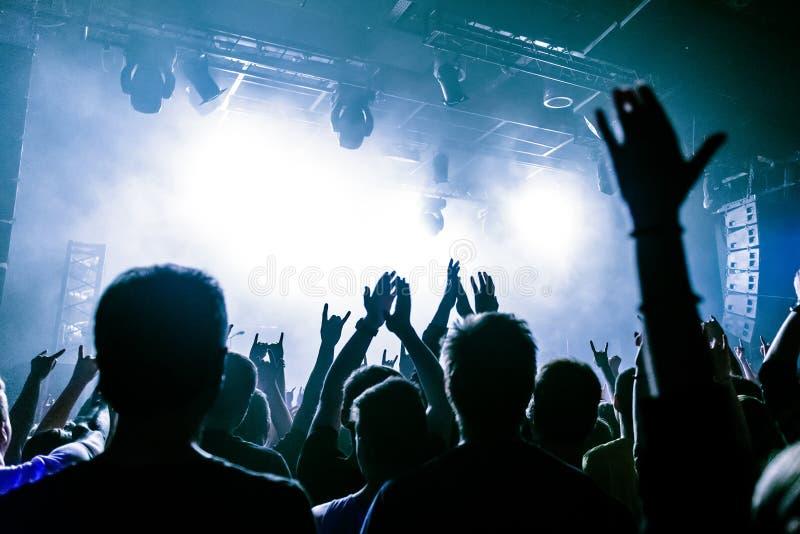 Silhouetten van mensen in helder in het pop rotsoverleg voor het stadium Handen met gebaarhoornen Dat schommelt Partij in a stock fotografie