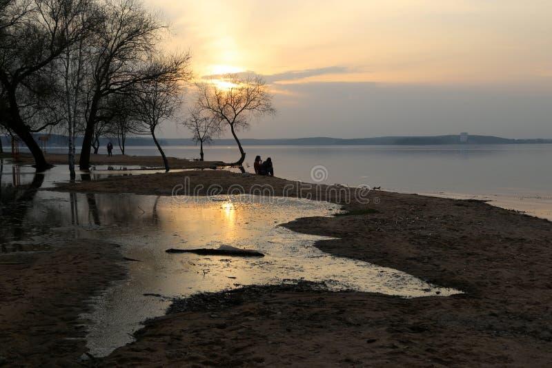 Silhouetten van mensen op het strand stock afbeelding